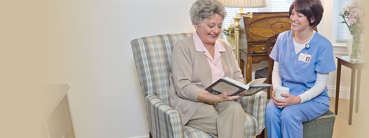 Brethren Village nurse and resident reading together